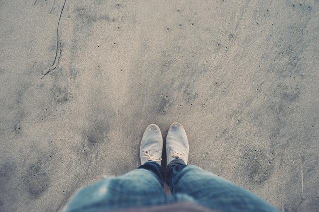 Mužské nohy v rifliach a sivých topánkach na piesku.jpg