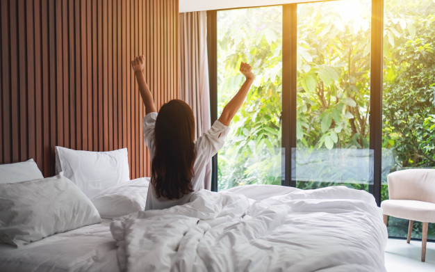 rear-view-woman-stretching-after-waking-up-morning-looking-beautiful-nature-view-outside-bedroom-window_9563-5435